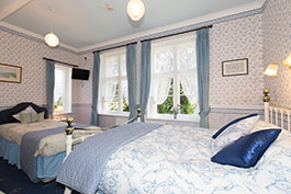 A family bedroom (double and a single bed) freshly decorated in blue.